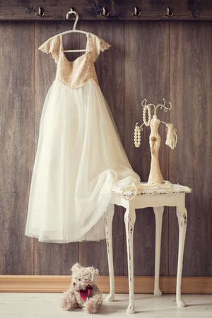 Little girls room with hanging dress and table with pearl necklace - vintage tone effect photo