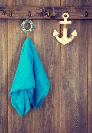 laundry room: Aqua blue towel hanging on bathroom door with anchor decoration