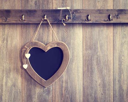 Heart shape menu board hanging on wooden panel wall - vintage tone effect added to wood Foto de archivo