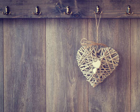 raffia: Rustic heart decoration hanging from hook on wood panel wall - vintage tone effect added