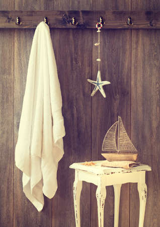 Bathroom with towel and toy boat on rustic table - vintage tone effect added photo