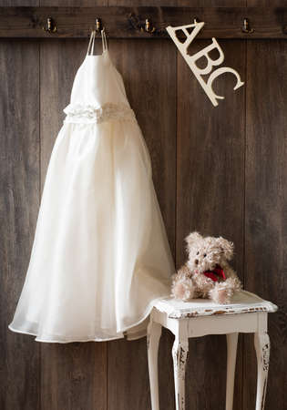 Pretty dress hanging in nursery with ABC letters and teddy bear sitting on table photo