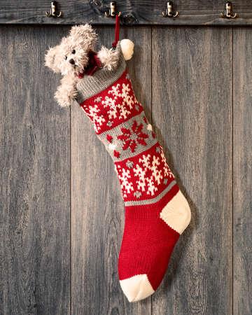 Kerst kous opknoping op de haak gevuld met teddybeer