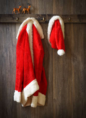 Santa's coat and hat hanging up with reindeer on ledge