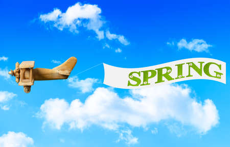 Vintage wooden toy plane flying in blue sky pulling a banner to bring in spring photo