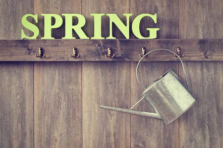 wood panelled: Watering can hanging in shed with the word Spring