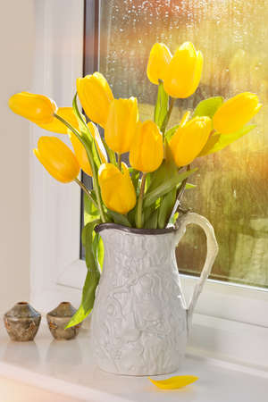 tulips in vase: Bright yellow tulips in antique jug sitting in window Stock Photo