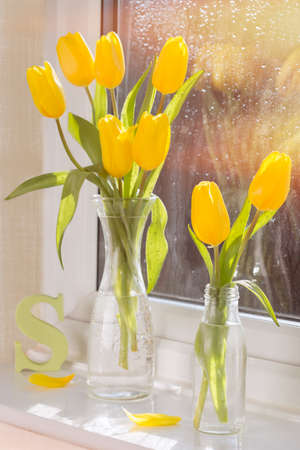 Spring tulips in retro glass bottles with letter S in the background photo
