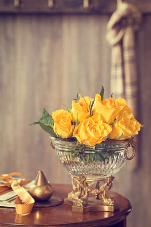 Yellow roses in antique vase sitting on hallway table photo