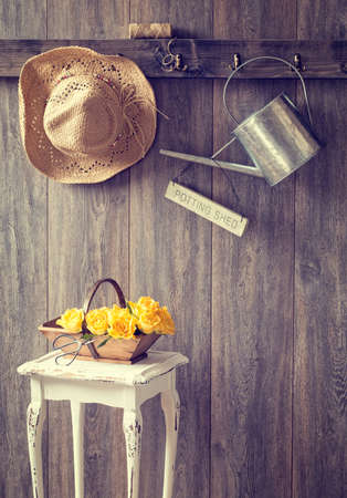 The potting shed with hanging straw hat and garden tools - vintage tone effect added photo