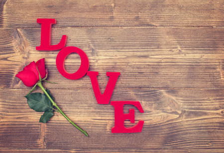 Single red rose and the word love on a rustic background Stock Photo
