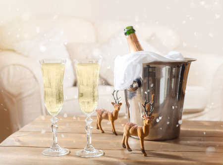 Two glasses of champagne with ice bucket and reindeer in background photo