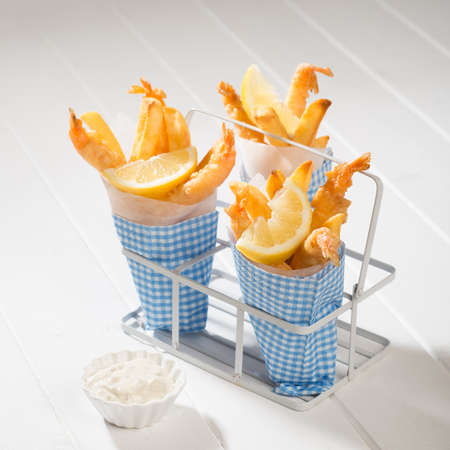 Cones of tempura prawns and fries with tartar sauce photo