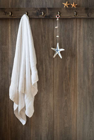 White towel hanging on bathroom wall with starfish decoration