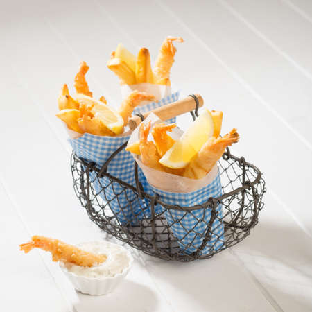 Fries and tempura prawns in a basket with tartar sauce on the side photo