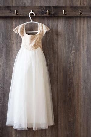 krajina: Holčičky šaty visí na háku na dřevěné obložené zdi Reklamní fotografie