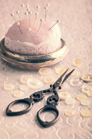 antique scissors: Antique scissors with button and pin cushion - vintage tone effect added Stock Photo
