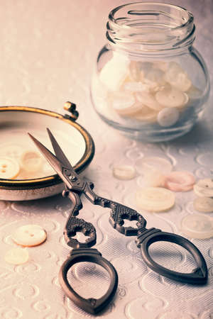 Antique sewing scissors with ivory buttons on damask material - vintage tone effect added  photo