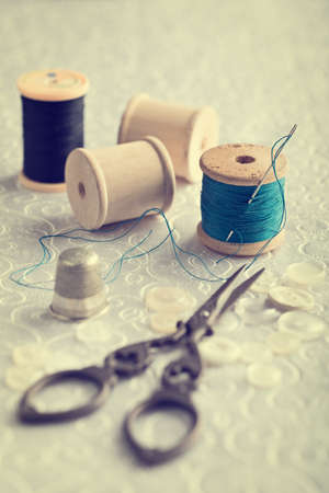 Threaded needle in cotton reel with sewing items - focus on threaded needle photo