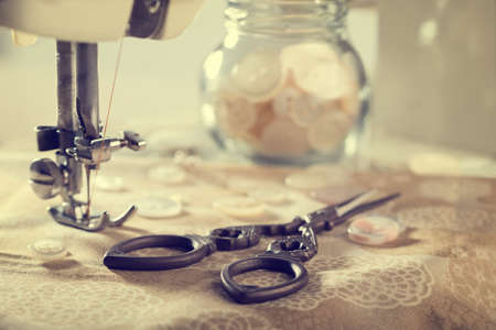 Vintage scissors with buttons and sewing machine - vintage tone effect added Stock Photo