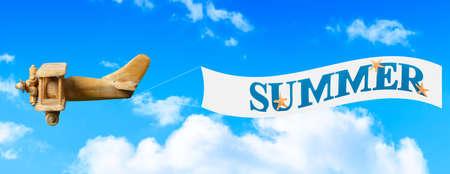 pull toy: Avión de juguete de madera de la vendimia volando en el cielo azul que tira de una bandera para llevar en verano