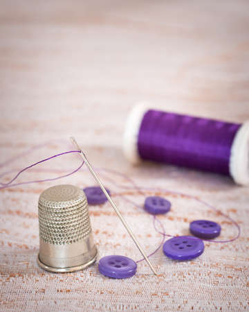 thimble: Antique silver thimble with threaded needle and purple buttons