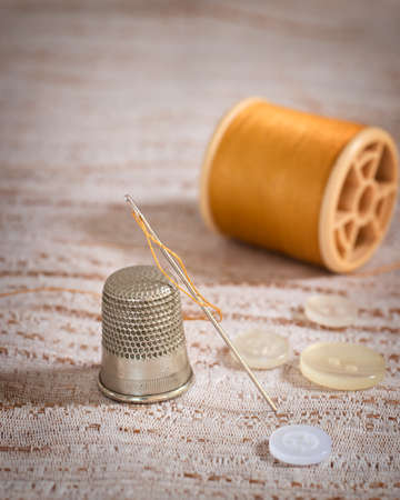 Threaded sewing needle with thimble and buttons photo