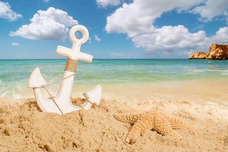 ancla: Ancla con estrellas de mar en una playa de arena - concepto de vacaciones de verano