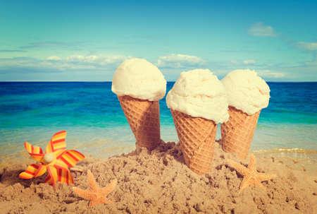 helado cucurucho: Helados de vainilla en la playa - efecto de tono retro nostálgico añadido