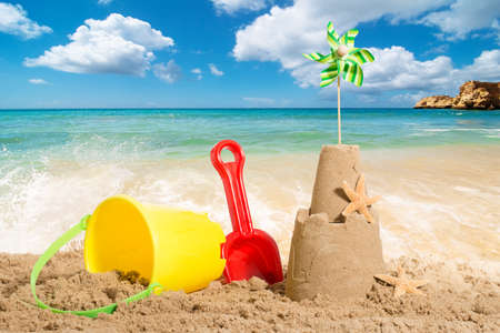 Sandcastle at the beach with bucket and spade Standard-Bild