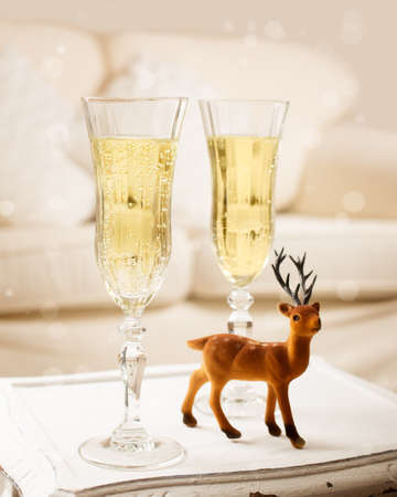 Two glasses of champagne on rustic table with reindeer Stock Photo