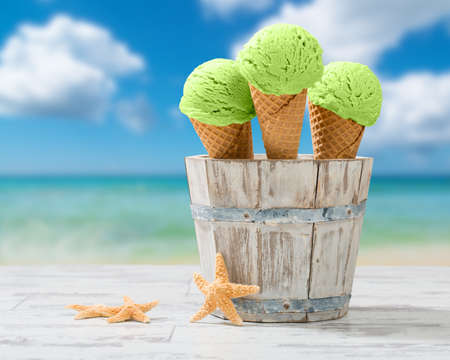Drie minij-ijsjes in rustieke emmer aan de kust Stockfoto