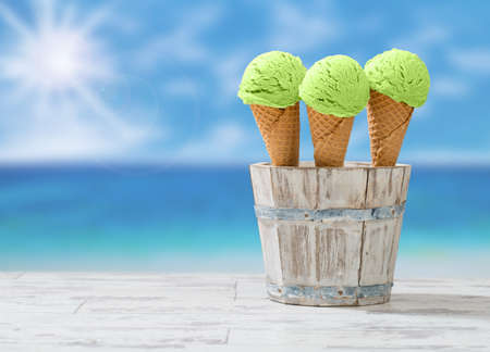 Mint ice creams in rustic wooden bucket at the beach with sun flare Stock Photo