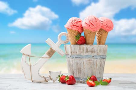Three strawberry ice creams with fruit at the beach Foto de archivo