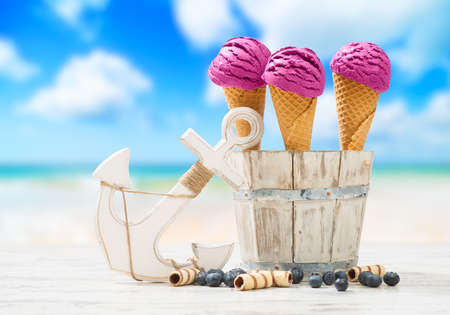 Icecreams with blueberries and anchor with beach blur background photo