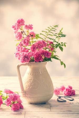 antique vase: Cut pink roses from the garden arranged in an antique vase - vintage filter effect added