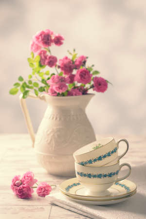 Vintage teacups with freshly picked pink roses from the garden - vintage tone added photo