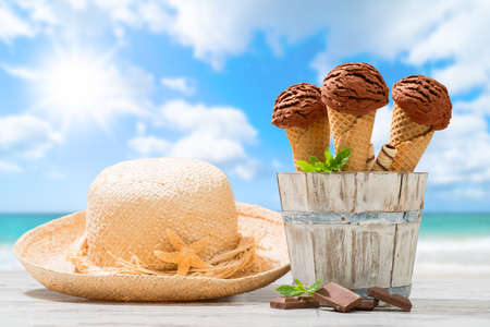 Chocolate flavor ice creams with sunhat and beach blur background