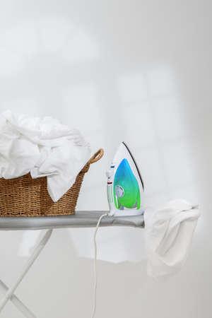laundered: Basket of freshly laundered washing and electric iron on board