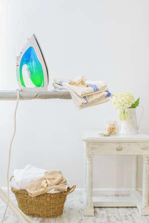 Bijkeuken in het huis met ijzer en mand van vers witgewassen wassen Stockfoto