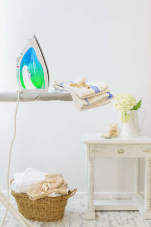 laundered: Utility room in the home with iron and basket of freshly laundered washing Stock Photo