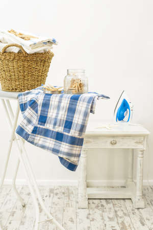 utility: Jar of clothes pegs and basket of fresh laundry with iron in the background Stock Photo