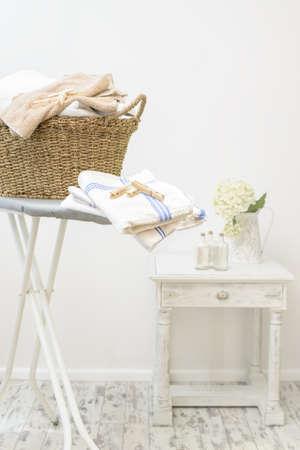 Strijkplank met een mand met wasgoed en haringen in de bijkeuken