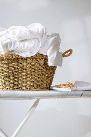Basket of freshly washed laundry on ironing board