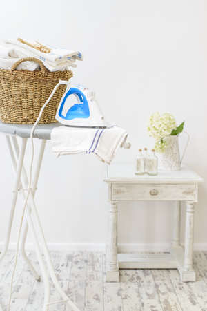 Laundry room in the home with iron and basket of washing Foto de archivo