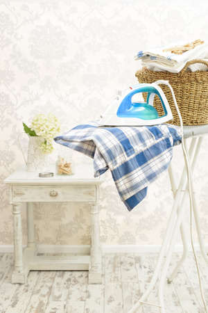 Freshly pressed clothes on the ironing board in laundry room  Stock Photo