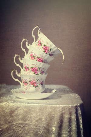 Stack of tilted vintage teacups with milk spilling out  photo