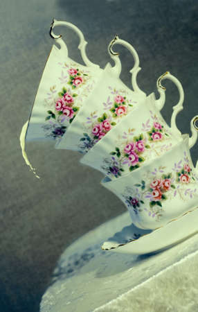 Extreme tilted antique teacups with vintage filter effect added photo
