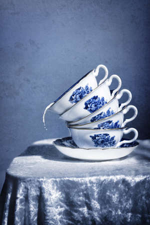 Stack of pretty blue and white vintage teacups with spilling milk photo
