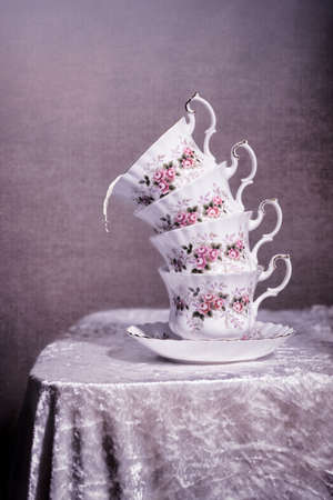Stack of antique cups with spilt milk - vintage tone filter effect added photo